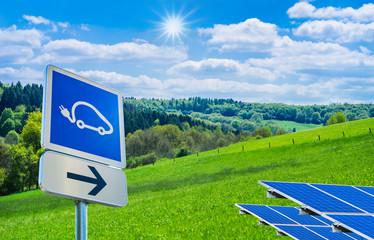 Wegweiser zur Solartankstelle für Autos vor traumhafter Landschaft mit strahlender Sonne - Trafic sign to the solar station for cars in front of a wonderfull landscape with a bright sun