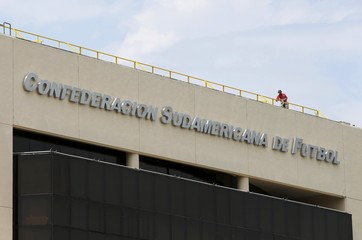 A worker stands on the roof of the headquarters of the South American Soccer Confederation (CONMEBOL) in Luque