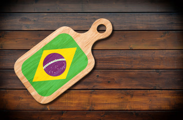 Concept of Brazilian cuisine. Cutting board with a Brazil flag on a wooden background