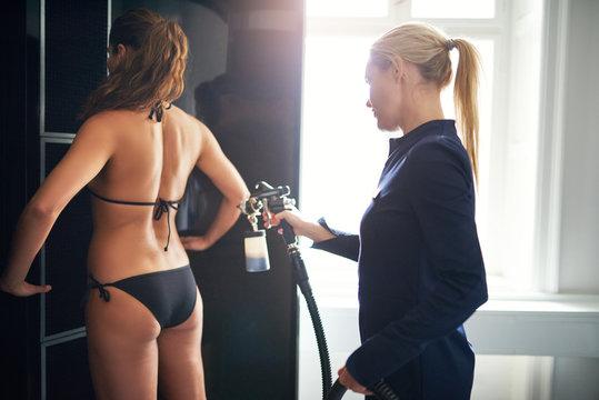 Beauty professional providing spraytan procedure to client