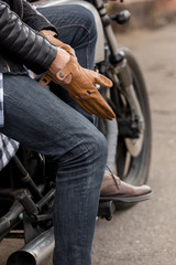 Close-up of a handsome rider biker man hand puts on a glove while sit on classic style cafe racer motorcycle. Bike custom made in vintage garage. Brutal fun urban lifestyle. Outdoor portrait.