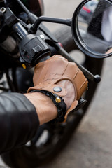 Foto op Plexiglas Closeup of a hipster biker man hand in leather glove hold throttle control of classic style cafe racer motorcycle. Bike custom made in vintage garage. Brutal fun urban lifestyle. Outdoor portrait.