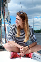 Smiling girl sitting on yacht deck. Attractive girl on a yacht at summer day