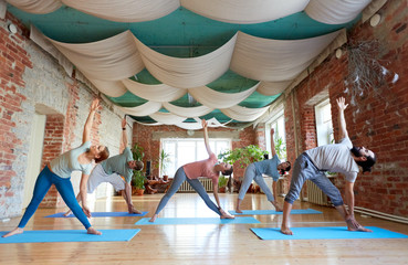 group of people doing yoga triangle pose at studio