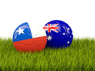 Two footballs with flags of Chile and Australia on green grass