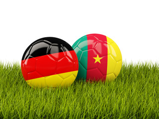 Two footballs with flags of Germany and Cameroon on green grass