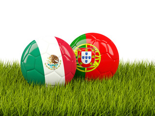 Two footballs with flags of Mexico and Portugal on green grass