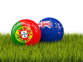 Two footballs with flags of Portugal and New Zealand on green grass