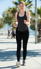 Sporty woman running along embankment