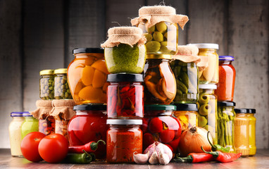 Jars with variety of pickled vegetables.