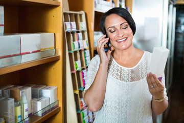 Woman chatting by phone while shopping in drugstore