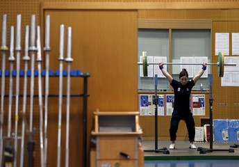 Japanese weightlifter Miyake, 30, is reflected in a mirror as she checks her lifting form during a training session at the National Training Center in Tokyo