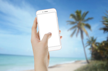 Woman holding smartphone with empty screen in hand with beach and sea in background