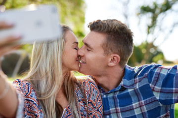 Young couple kiss and take selfie in park