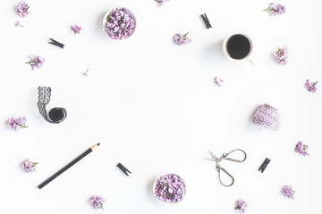 Stylish feminine workspace with lilac flowers, cup of coffee, accessories. Flat lay, top view