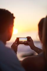 Couple take photo of beautiful sunset on smart phone