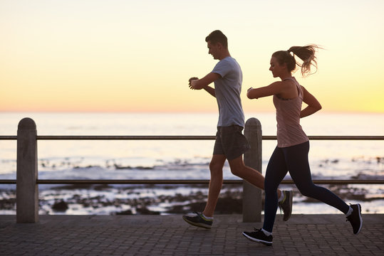 Athletic couple tracking their run at sunset