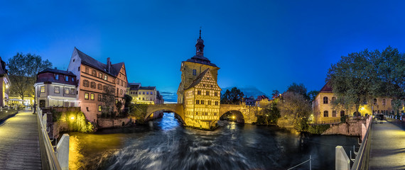 Bamberg. Panoramic view of Old Town Hall of Bamberg (Altes Rathaus) with two bridges over the Regnitz river in the evening, Germany