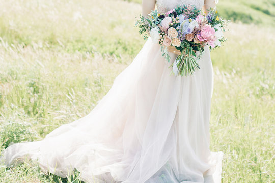 fine art wedding photography. Beautiful bride with bouquet and dress with train in nature