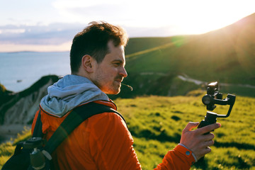 Young man taking a travel video using mobile phone and gimbal