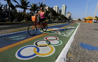 Woman rides her bicycle as she passes over a painting of Olympic rings ahead of the Rio 2016 Olympic games near Barra da Tijuca beach in Rio de Janeiro