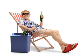 Elderly tourist with bottle of beer sitting in deck chair