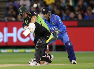 Australia's Aaron Finch hits a six while batting with India's Mahendra Singh Dhoni watching during their T20 cricket match at the Melbourne Cricket Ground