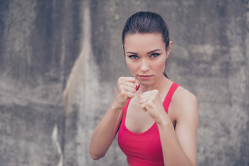 Woman power, self defence concept. Close up portrait of attractive serious fit boxer, ready for fight, on concrete wall background, wearing pink fashionable sport we