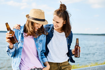 Friendship - two cheerful young woman enjoying summer vacation, drinking beer