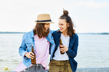 Two joyful young woman drinking beer during summer day