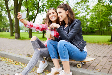 Friendship - Happy young women siting together on longboard in park taking selfie