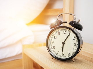 Alarm clock , wake-up time concept : Retro alarm clock with five minutes past six o'clock in the morning on wooden bed side table with white bed sheet and morning sunlight background