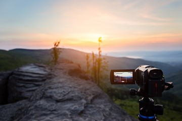 Digital video camera on tripod filming sunrise at mountains.