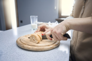 Woman cuts bread in the kitchen