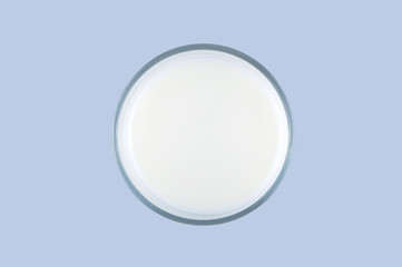 Top view of a glass of milk isolated on the light blue background