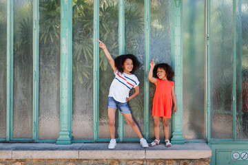 Smiling sisters dancing in front of a green wall