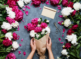 Female florist holding beautiful bouquet at flower shop. Florist at work: pretty woman making summer bouquet of peonies on a working gray table. Kraft paper, scissors, envelope for congratulations. Fototapete