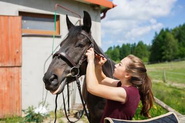 The rider saddles a horse