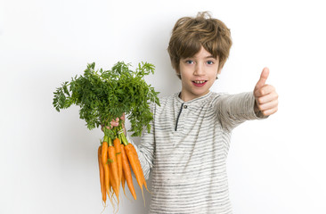 Boy is showing a thumb up while holding bunch of carrots in other hand
