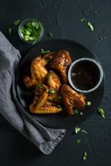 Fried chicken wings with sauce and chopped herbs