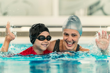 Cheerful boy with swimming instructor