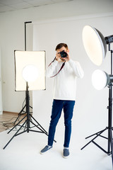 Young male photographer in studio
