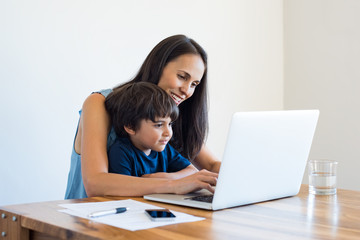 Mother working at home with son