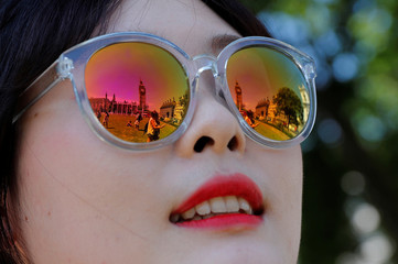 The Houses of Parliament are reflected in the sunglasses of a woman in Westminster, central London