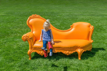 Little girl kicking off her boots getting ready to relax on a big orange sofa