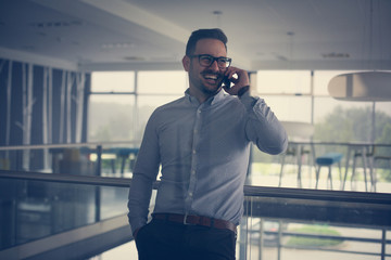 Business man standing in business building. Business man talking on smart phone.