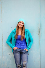 Smiling young woman teenager hands in pockets, on gray background, looking at camera