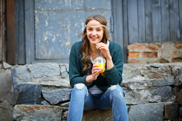 Laughing hipster girl, sitting on stone steps, holding orange juice, healthy lifestyle, fun, lifestyle