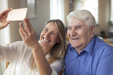 Woman taking selfie with grandfather