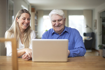 Young woman and grandfather using laptop